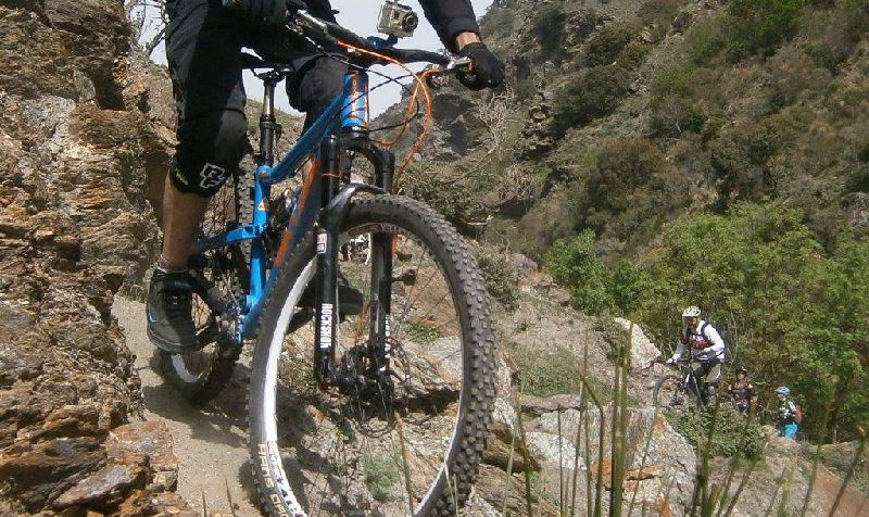 photo of mountain bike descending a technical trail
